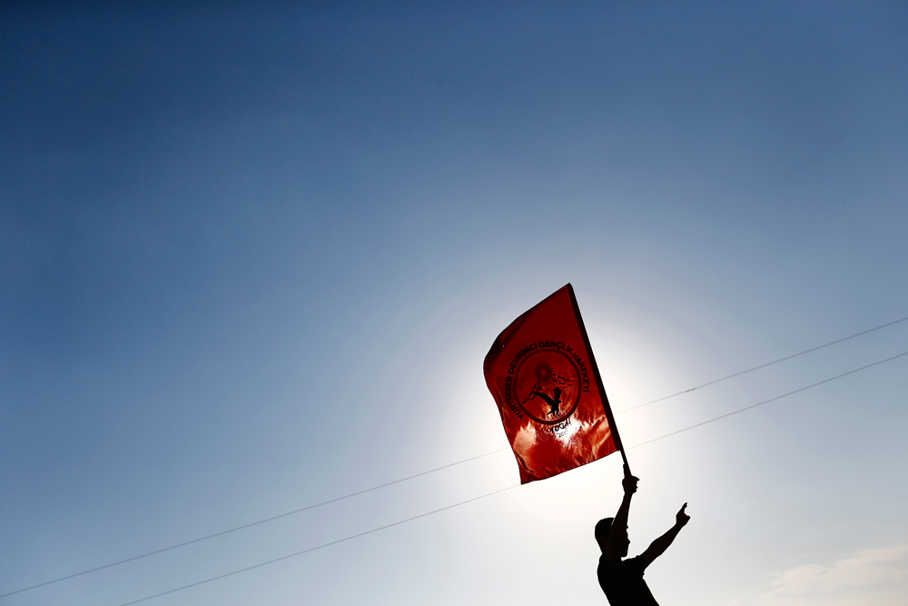 Un ragazzo sventola la bandiera del PKK a Kobane
